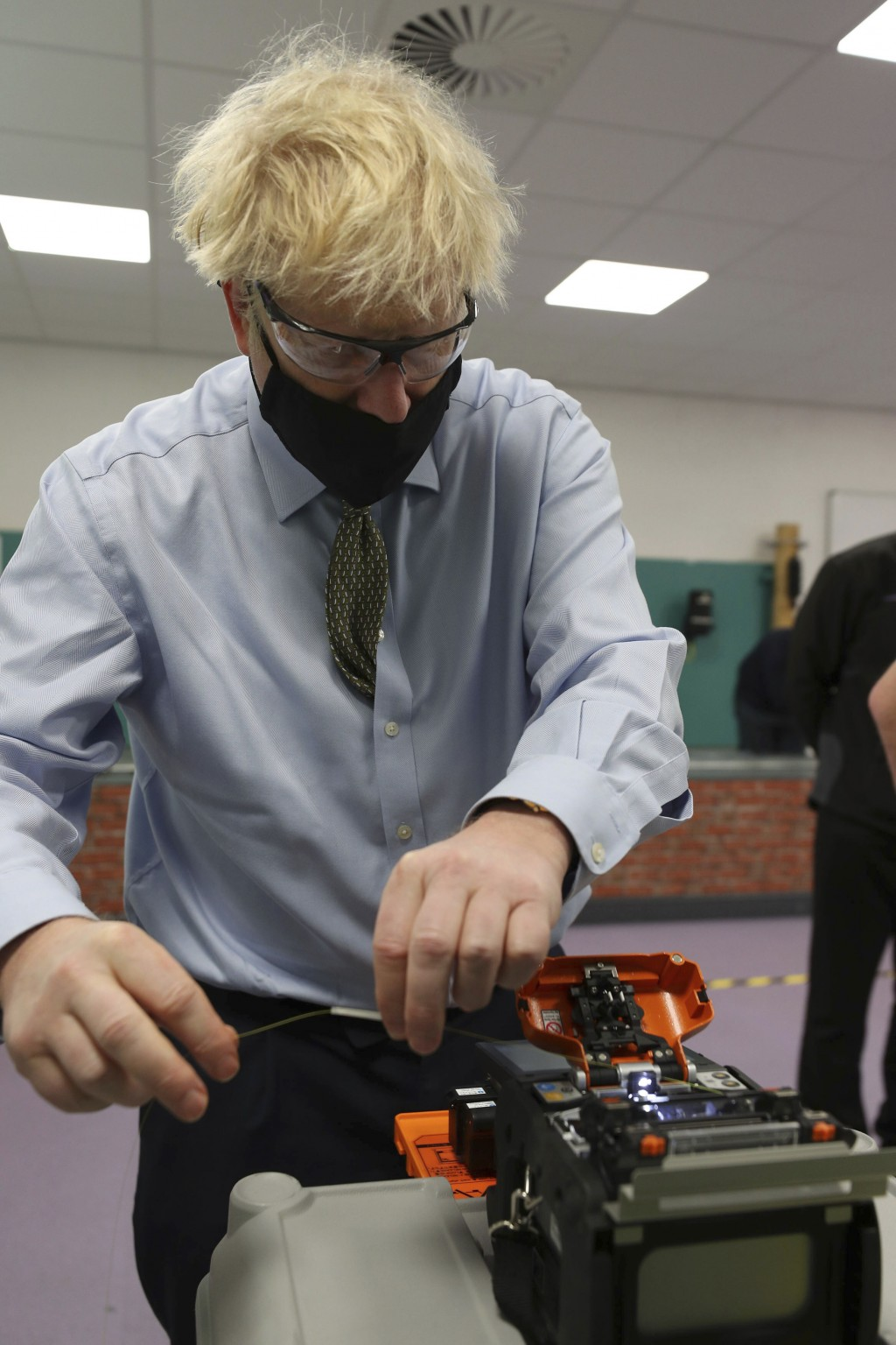 Britain's Prime Minister Boris Johnson tries his hand at cable splicing, during a visit to the Openreach L and D Training Centre in Bolton, England, F...