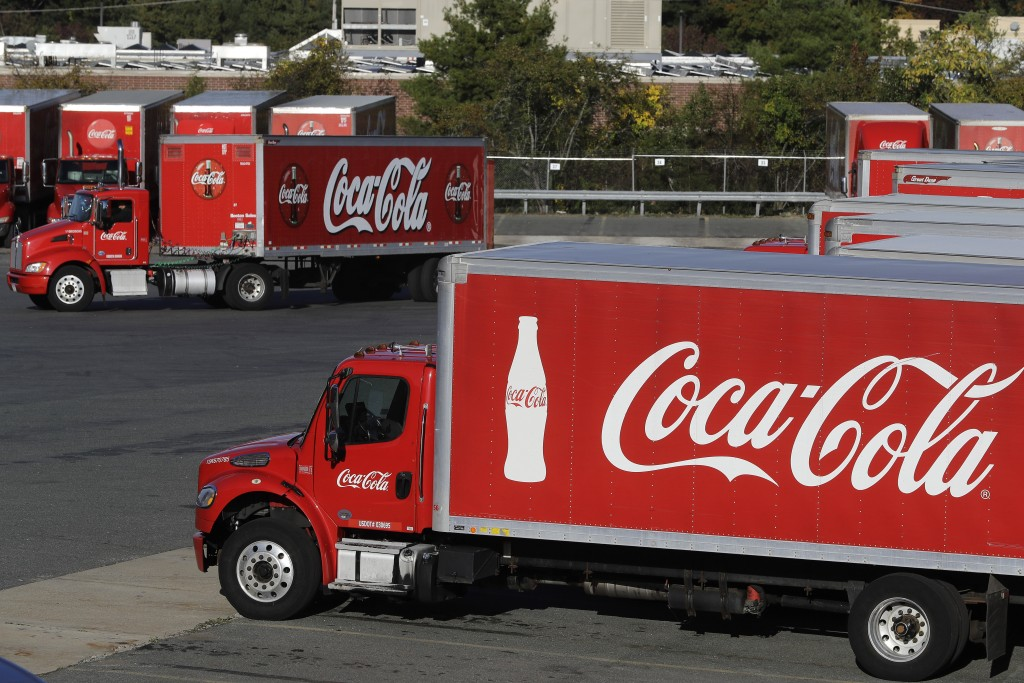 FILE - In this Oct. 14, 2019 photo a truck with the Coca-Cola logo, behind left, maneuvers in a parking lot at a bottling plant in Needham, Mass. The ...