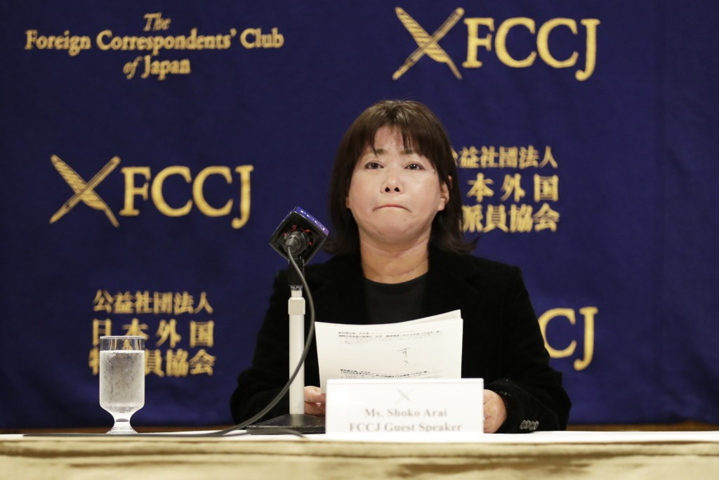 Shoko Arai, a former councilwoman in Kusatsu town, northwest of Tokyo, bites her lips while speaking during a news conference in Tokyo Friday, Dec. 18...