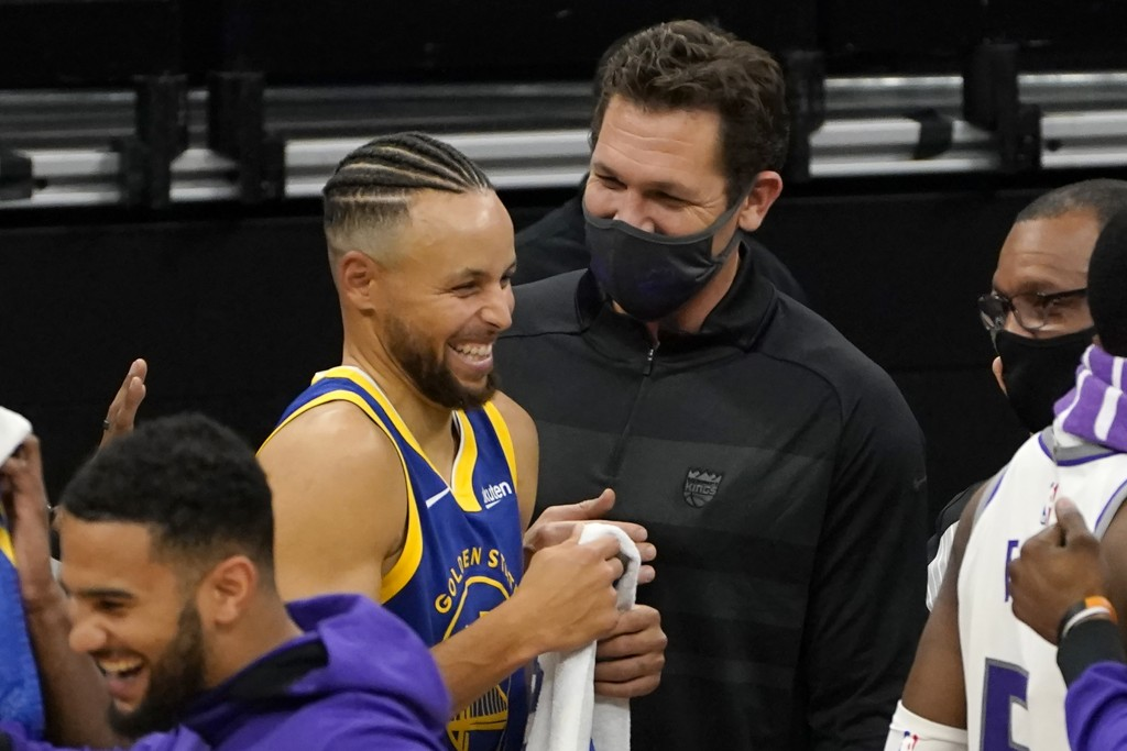 Golden State Warriors guard Stephen Curry, center left, laughs during a conversation with Sacramento Kings head coach Luke Walton after the Warriors b...