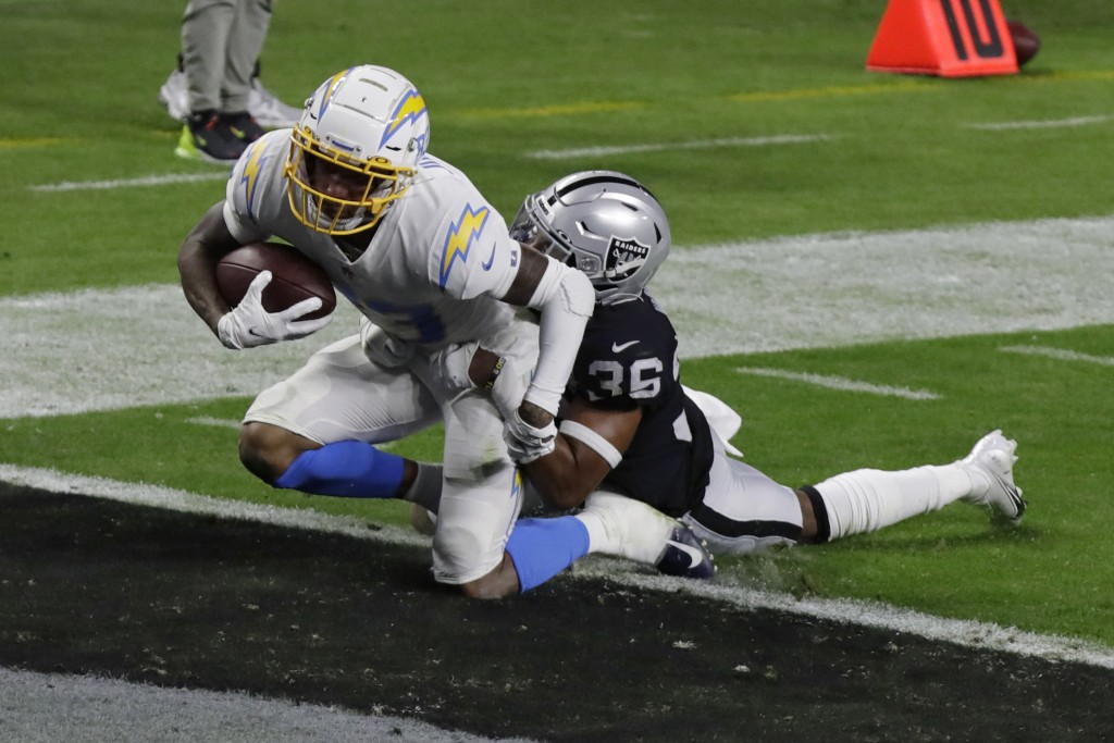 Los Angeles Chargers wide receiver Tyron Johnson (83) scores a touchdown against Las Vegas Raiders' Daryl Worley during the first half of an NFL footb...