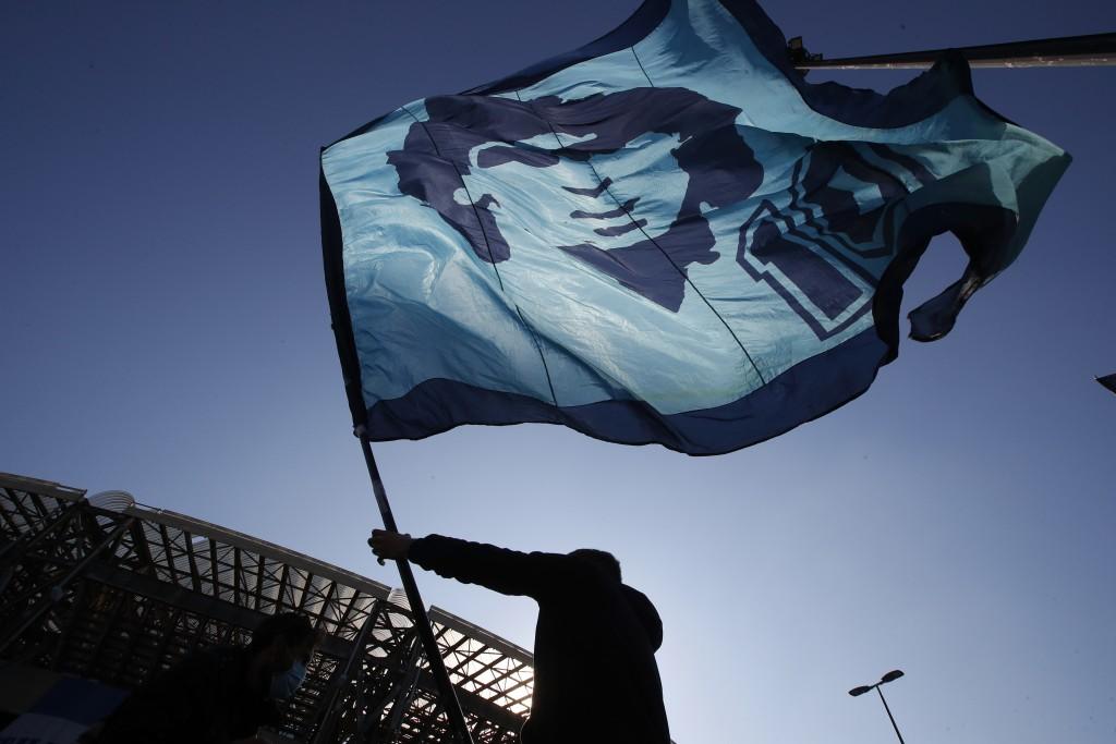A man waves a flag commemorating soccer legend Diego Maradona outside the San Paolo stadium, in Naples, southern Italy, Thursday, Nov. 26, 2020. Marad...