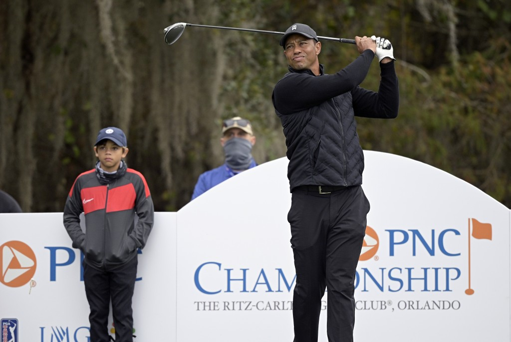 Tiger Woods, right, tees off on the 12th hole as his son Charlie, left, watches during a practice round of the Father Son Challenge golf tournament, T...