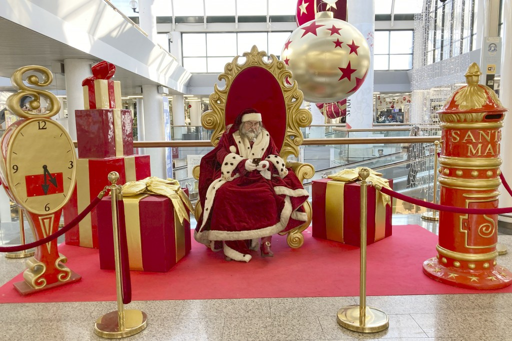 A man wearing a Santa Claus costume checks his mobile phone as he waits to pose for pictures at a mall in Rome, Friday, Dec. 18, 2020. The health mini...