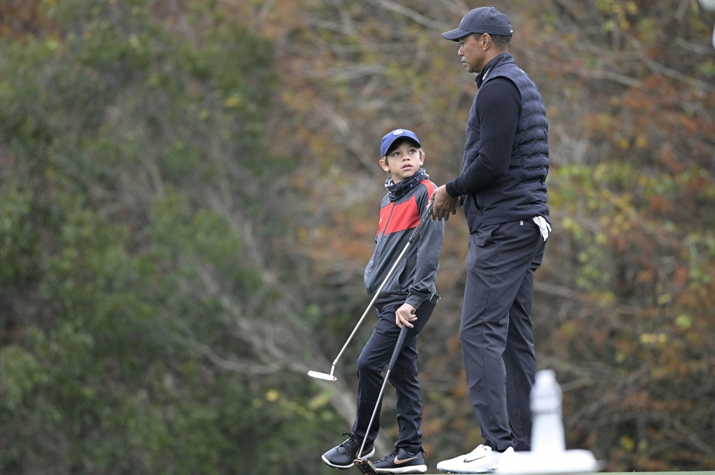 Tiger Woods, right, chats with his son Charlie on the 11th green during a practice round of the Father Son Challenge golf tournament, Thursday, Dec. 1...