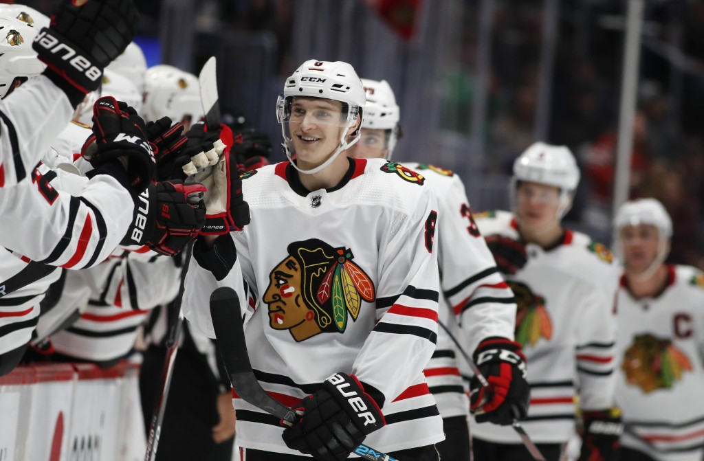 FILE - Chicago Blackhawks left wing Dominik Kubalik, center, smiles as he is congratulated while passing the team box after scoring the go-ahead goal ...