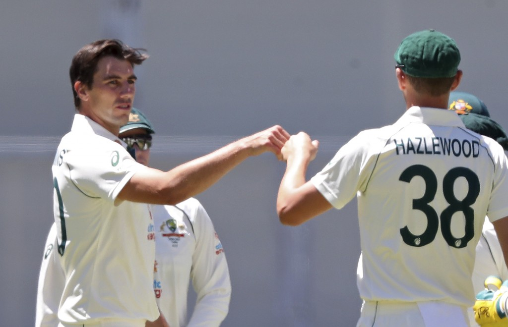 Australia's Pat Cummins, left, is congratulated by teammate Josh Hazlewood after taking the wicket of India's Ravichandran Ashwin on the second day of...