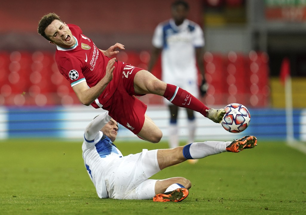 Liverpool's Diogo Jota reacts as he is tackled by Atalanta's Marten de Roon during the Champions League group D soccer match between Liverpool and Ata...