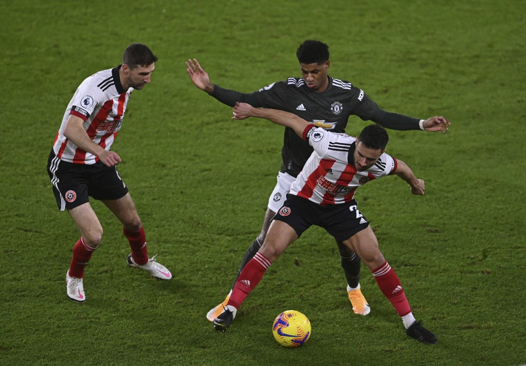 Sheffield United's George Baldock, right, tries to control the ball in front of Manchester United's Marcus Rashford, as Sheffield United's Chris Basha...