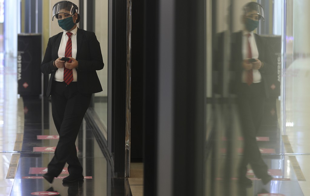 A woman employee wearing a mask and face shield stands outside a shop in mall in Mumbai, India, Friday, Dec. 18, 2020. (AP Photo/Rafiq Maqbool)