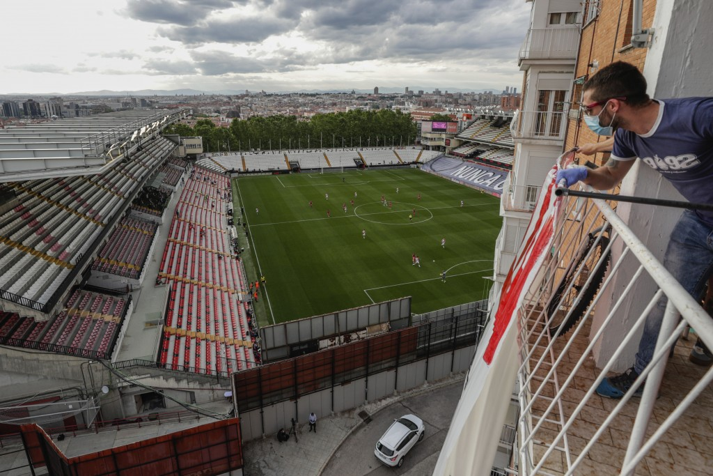 A man on a balcony watches the second-division game between Rayo Vallecano and Albacete in Madrid, Spain, Wednesday, June 10, 2020. With virtual crowd...