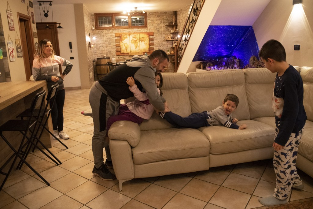 Nurse Maurizio di Giacobbe plays with his children from left, Arianna, 9, Tiziano, and Flavio 10, as his wife Glenda Grossi looks at them, at their ho...