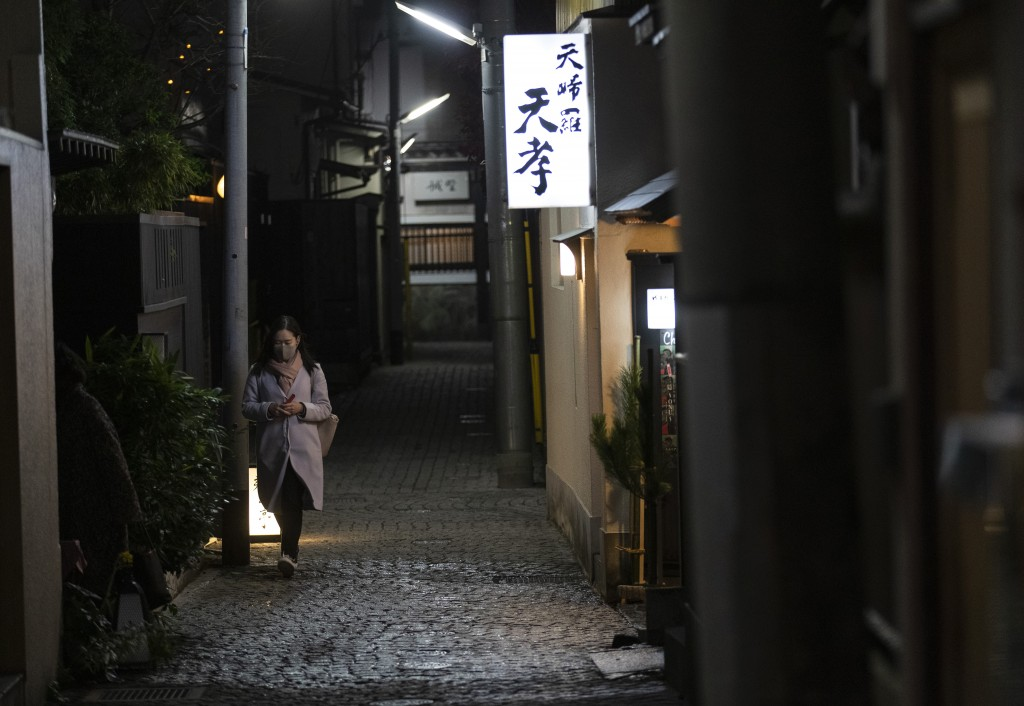 A woman wearing a face mask to help curb the spread of the coronavirus walks through an alley in Tokyo Friday, Dec. 18, 2020. (AP Photo/Hiro Komae)
