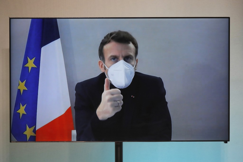 French President Emmanuel Macron is seen on a screen as he attends by video conference a round table for the National Humanitarian Conference (NHC), t...