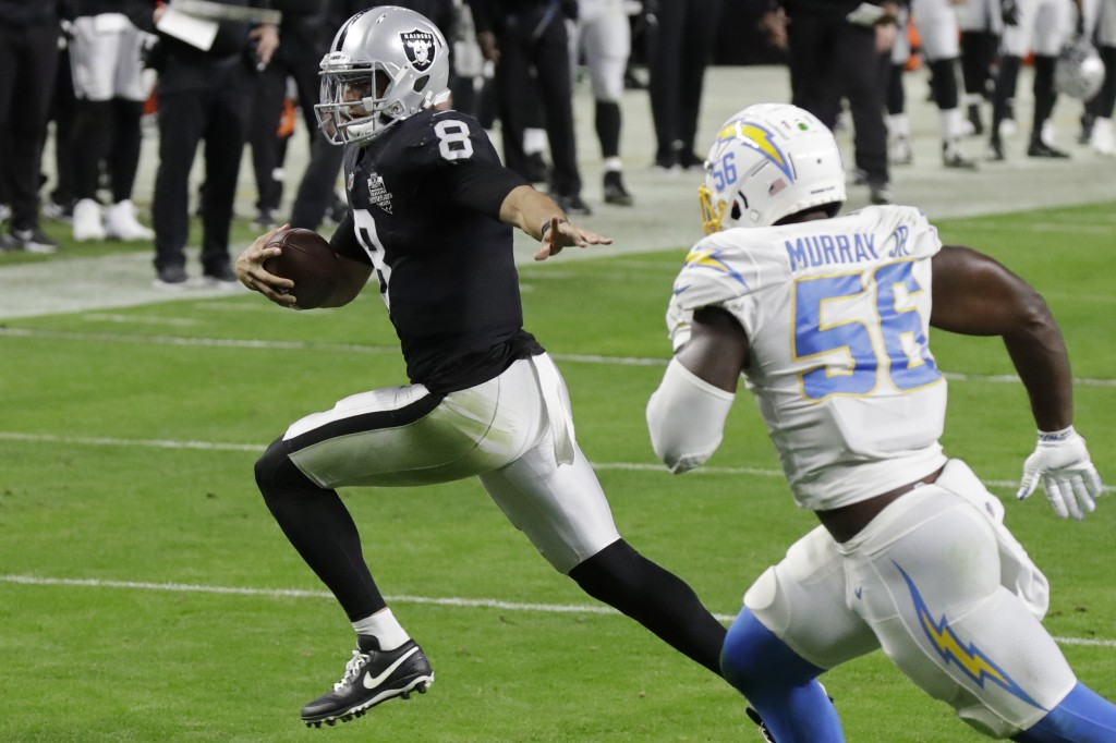 Las Vegas Raiders quarterback Marcus Mariota (8) runs for a touchdown against the Los Angeles Chargers during the second half of an NFL football game,...
