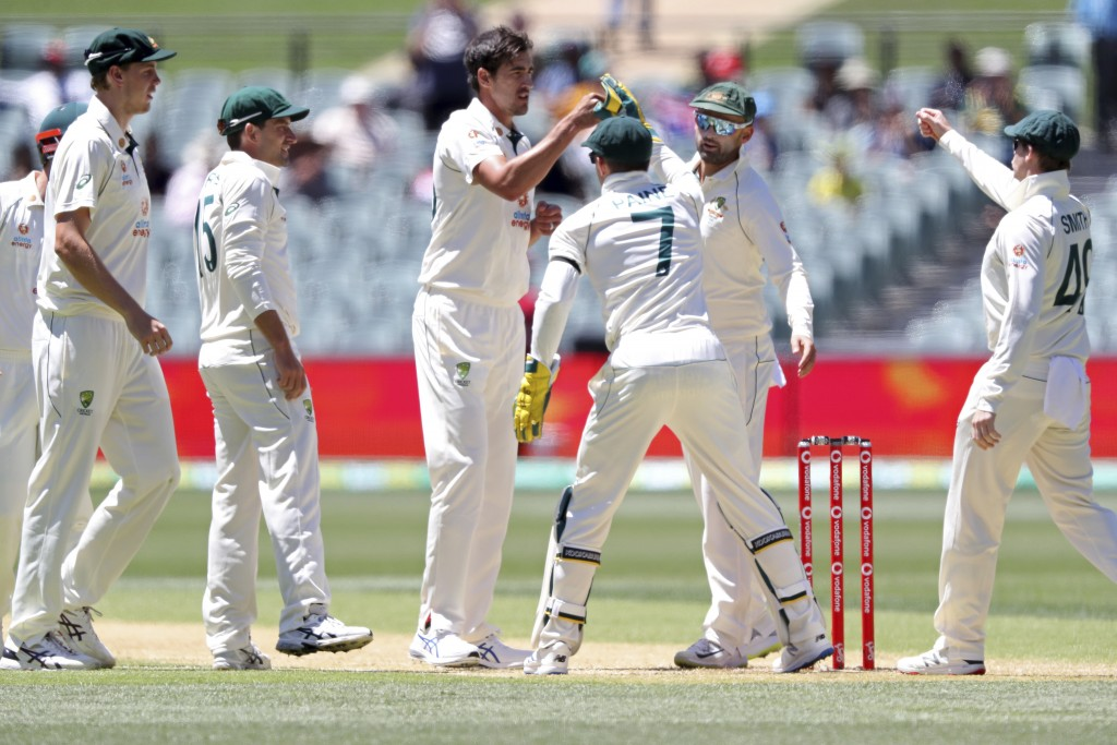 Australia's Mitchell Starc, center, is congratulated by teammates after taking the wicket of India's Wriddhiman Saha on the second day of their cricke...
