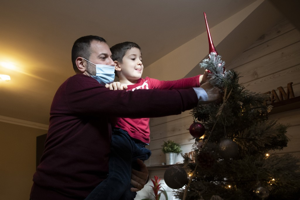Maurizio Di Giacobbe holds his 4-year old son Tiziano as they place decorations on a Christmas tree, in their house in the outskirts of Rome, Saturday...