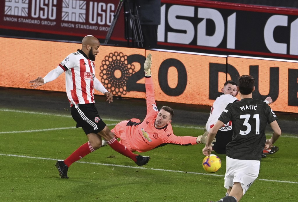 Sheffield United's David McGoldrick, left, shoots to score, as Manchester United's goalkeeper Dean Henderson, center tries to stop him, during the Eng...