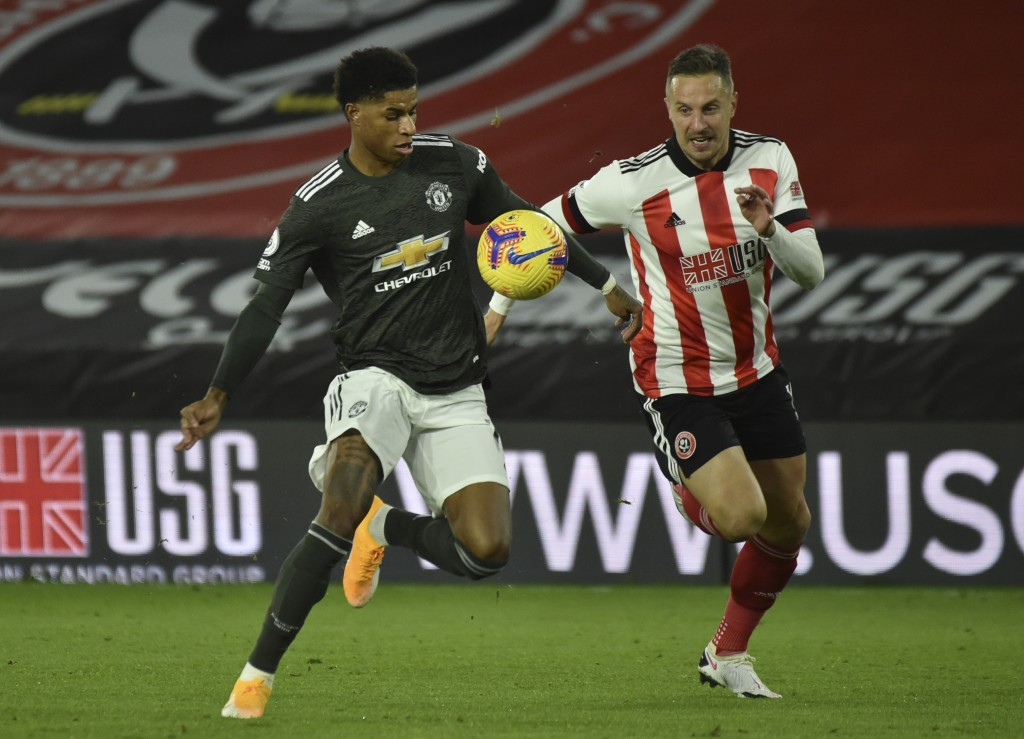 Manchester United's Marcus Rashford, left, fights for the ball with Sheffield United's Phil Jagielka, during the English Premier League soccer match b...