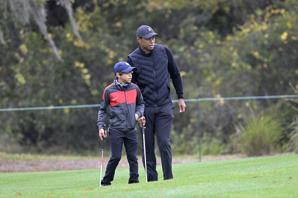 Tiger Woods, right, lines up a shot with his son Charlie on the 12th green during a practice round of the Father Son Challenge golf tournament, Thursd...