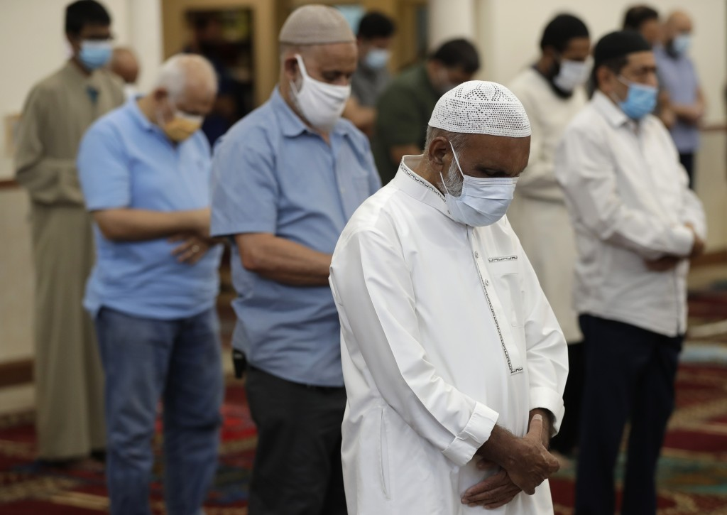 FILE - In this Friday, June 5, 2020 file photo, Muslim men pray at the Islamic Center of Greater Miami in Miami Gardens, Fla., social distancing and w...