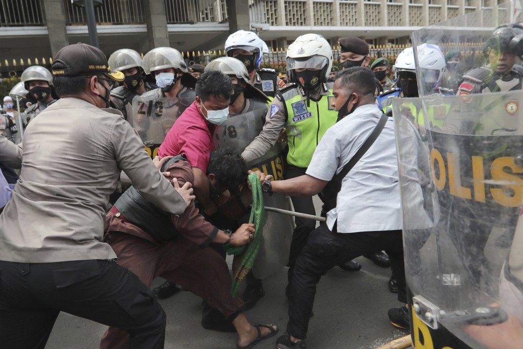 Supporters of Rizieq Shihab, leader of the Islam Defenders Front, scuffle with police officers during a rally in Jakarta, Indonesia, Friday, Dec. 18, ...