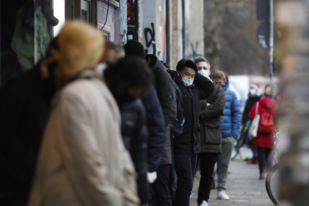 People wait in a long line for a SARS CoV-2 rapid test at the Corona Antigen Rapid test center at the 'KitKat-Club' in Berlin, Germany, Thursday, Dec....