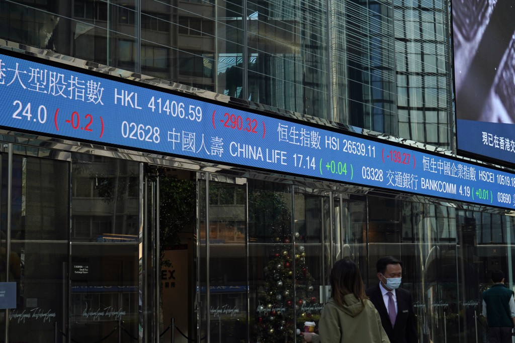 People wearing face masks walk past a electronic board showing the Hong Kong share index at the Hong Kong Exchange Square, Friday, Dec. 18, 2020. Asia...