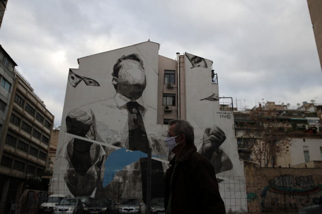 "A pedestrian wearing a face mask against the spread of coronavirus, walks in front of the graffiti ""Snowblind"" by the artist Ino in Athens, Friday, De..."