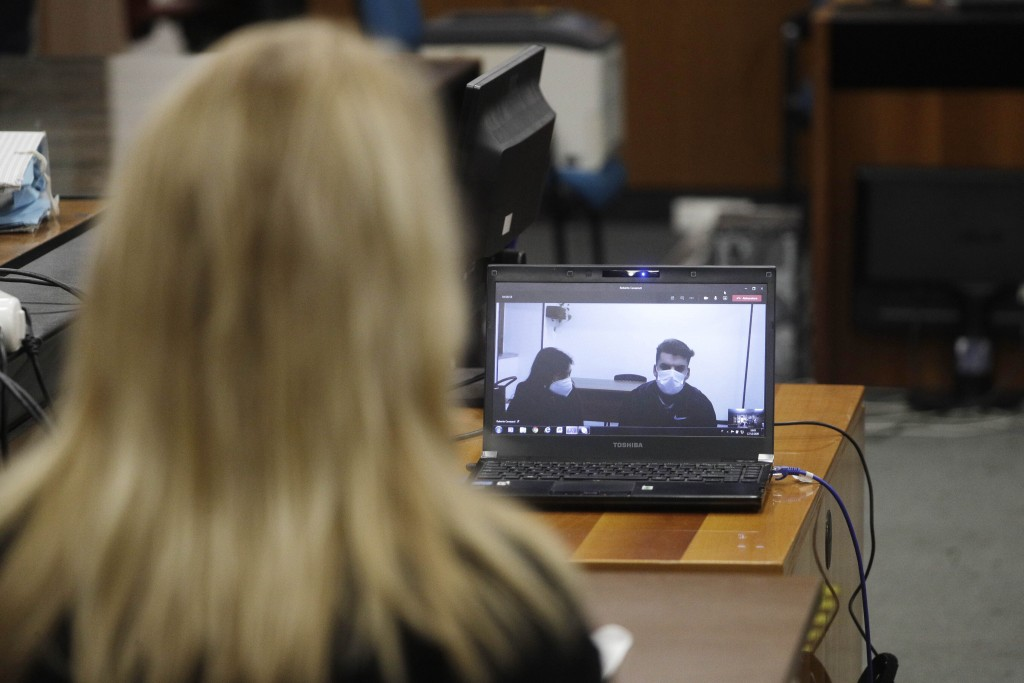 Gabriel Natale-Hjorth, right, connected from the jailhouse to the courtroom, listens to her mother Heidi Hjorth, during a hearing in the trial in whic...
