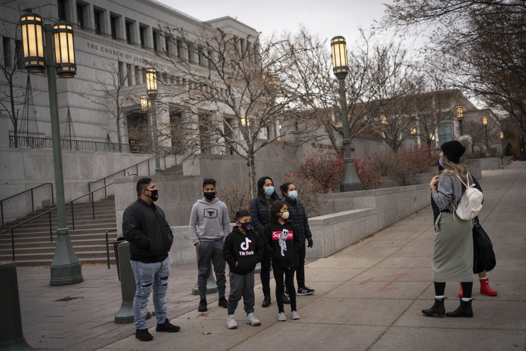 Members of The Church of Jesus Christ of Latter-day Saints speak to tourists around Temple Square in Salt Lake City, Sunday, Nov. 15, 2020. While the ...