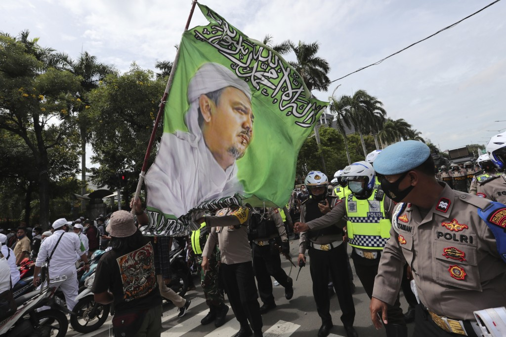 Supporters of Rizieq Shihab, leader of the Islam Defenders Front, display a flag bearing his image during a rally in Jakarta, Indonesia, Friday, Dec. ...