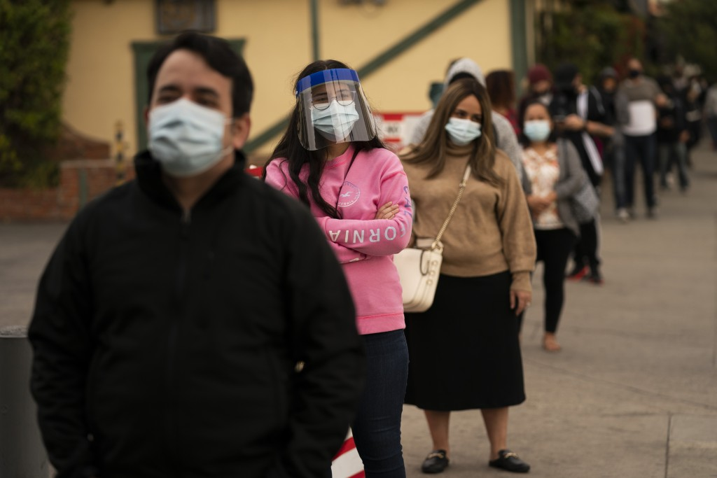 FILE - In this Dec. 7, 2020, file photo, people wait in line for COVID-19 testing at a testing site operated by CORE in Los Angeles. Hospitals across ...