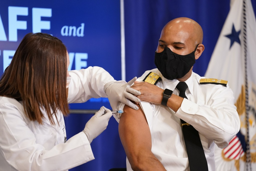 U.S. Surgeon General Jerome Adams receives a Pfizer-BioNTech COVID-19 vaccine shot at the Eisenhower Executive Office Building on the White House comp...