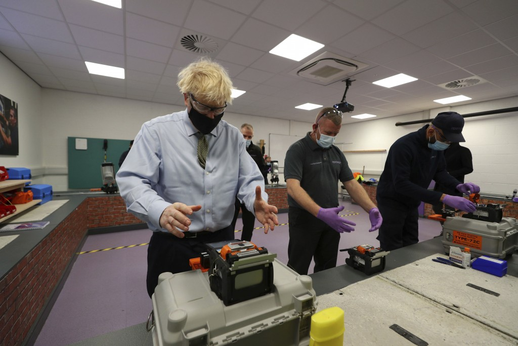 Britain's Prime Minister Boris Johnson, meets apprentice Talha Batan, right and instructor Colin Wilkinson, centre, giving a demonstration of cable sp...