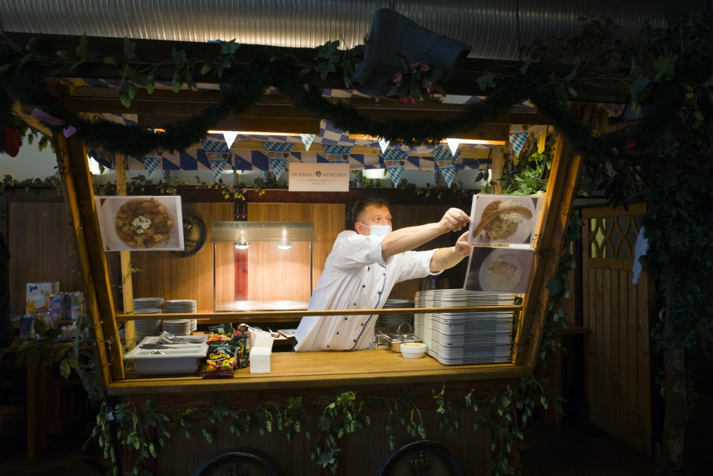 Cook Sascha Richter puts up photos of the menu at the food distribution station for the homeless people at Berlin's biggest restaurant Hofbraeu Berlin...