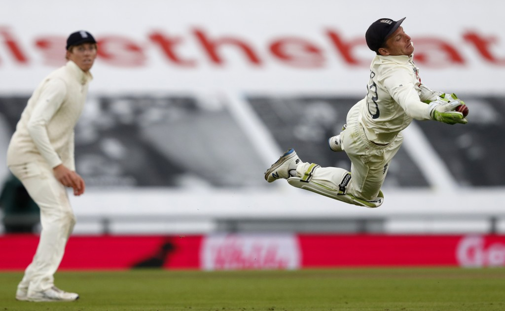 England's wicketkeeper Jos Buttler, right, dives to take the catch to dismiss Pakistan's Shaheen Afridi during the third day of the third cricket Test...