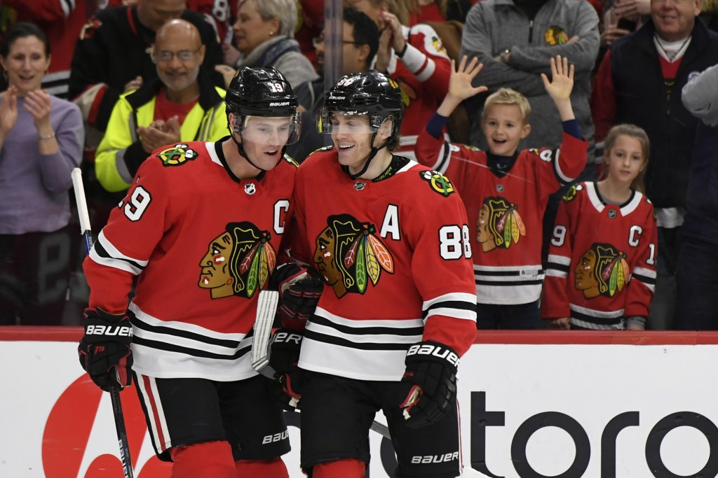 FILE - Chicago Blackhawks' Patrick Kane (88) celebrates with teammate Jonathan Toews (19) after scoring a hat trick during the third period of an NHL ...