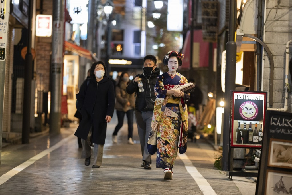 A geisha walks towards a place to perform her musical skills as people wearing face masks o protect against the coronavirus walk around an area filled...