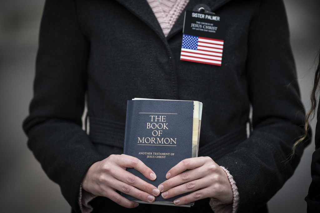 Sister Palmer, 19, holds The Book of Mormon while walking around Temple Square in Salt Lake City, Sunday, Nov. 15, 2020. Palmer, a member of The Churc...
