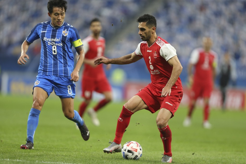 Ulsan Hyundai's Sin Jin-Ho, left, and Amir Roustaei of Persepolis fight for the ball during the AFC Champions League final match in Al Wakrah, Qatar, ...