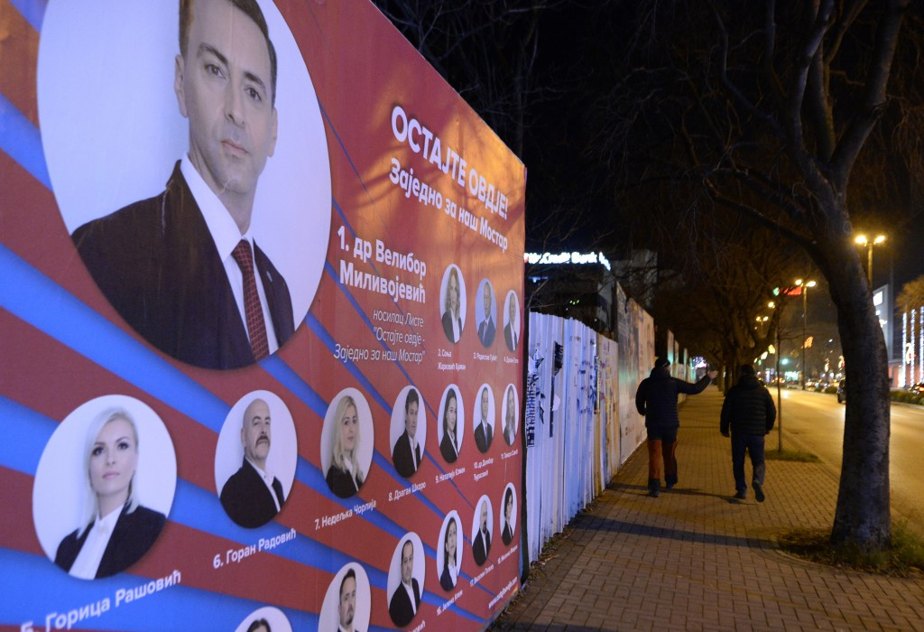 Two men pass by pre-elections billboards in Mostar, Bosnia, Friday, Dec. 18, 2020. Bosnia's ethnically divided southern city of Mostar is holding its ...