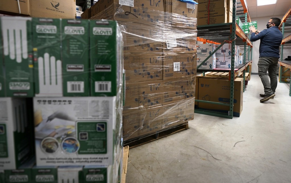 Ray Bellia stocks shelves with personal protective gloves, used by medical and law enforcement professionals, while unpacking pallets of other PPE goo...