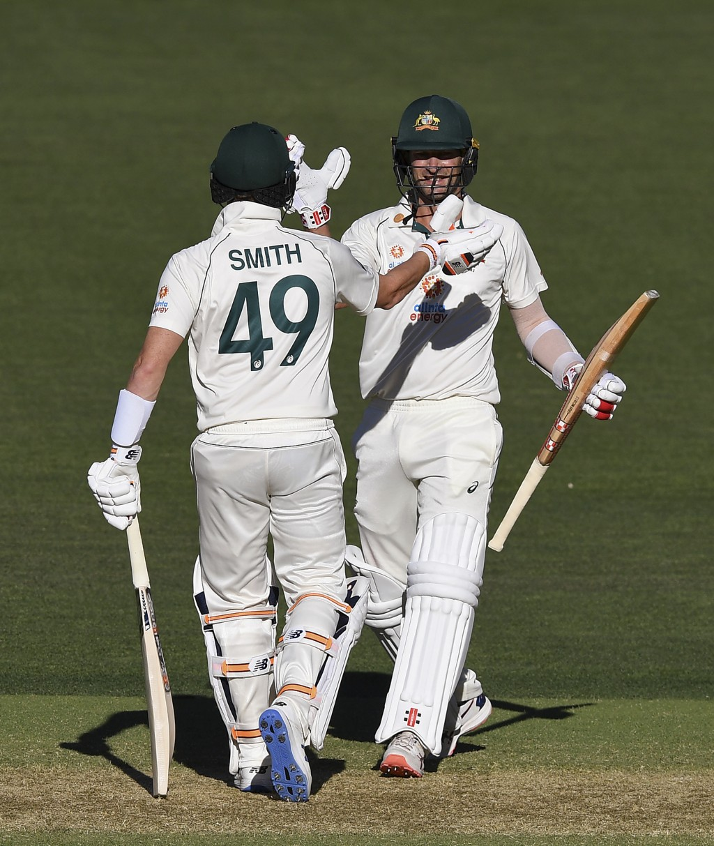 Australia's Joe Burns, right, is congratulated by teammate Steve Smith after hitting a 6 to win their cricket test match against India on the third da...