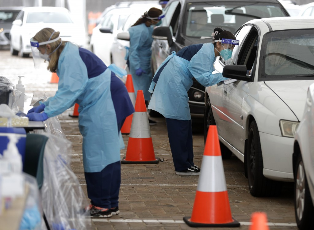 People attend a drive through COVID-19 testing station at a beach in Sydney, Australia, Saturday, Dec. 19, 2020. Sydney's northern beaches will enter ...