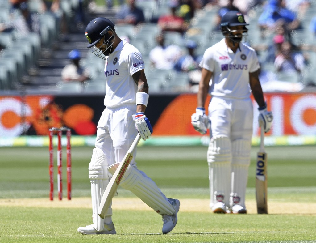 India's Virat Kohli, left, begins to walk off after he was caught out for 4 runs against Australia on the third day of their cricket test match at the...