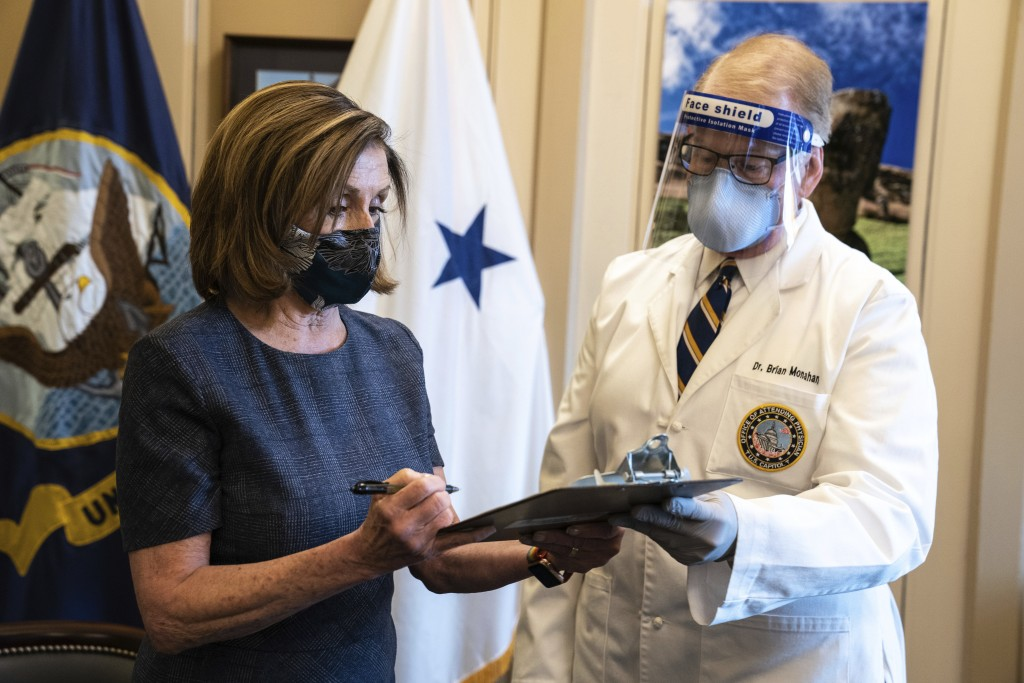 Speaker of the House Nancy Pelosi, D-Calif., signs a form next to Dr. Brian Monahan, attending physician Congress of the United States after she recei...