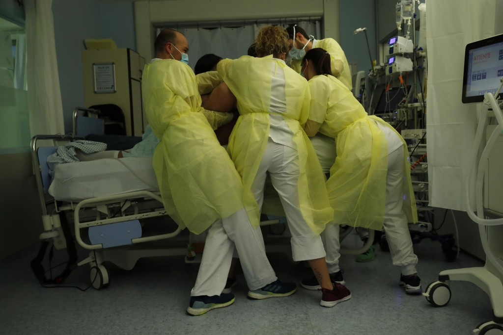 Nurse Anne-Catherine Charlier, right, and co-workers, wearing personal protection equipment, work in the intensive care ward for COVID-19 patients at ...