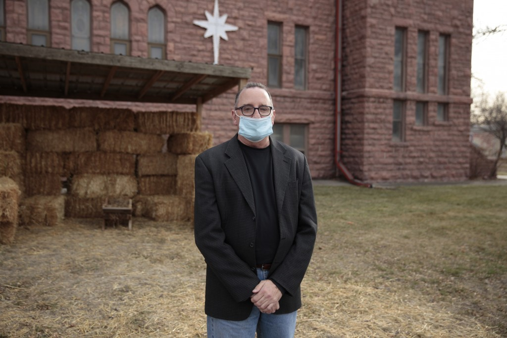 Rev. Tim Thies poses in front of the empty Nativity stable at Canton Lutheran Church in Canton, South Dakota on Dec. 8, 2020. The church decided to ca...