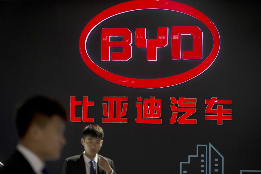 FILE - In this April 25, 2016, file photo, staff members stand near a logo for the BYD auto company as they wait for visitors at the Beijing Internati...